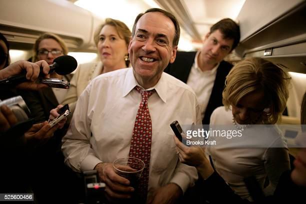Republican presidential candidate Mike Huckabee talks to the media with his wife Janet on his campaign plane en route to New Hampshire, after his...