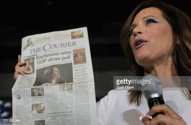 Republican presidential candidate Minnesota congresswoman Michele Bachmann holds up a copy of the local paper with her picture on the front as she...