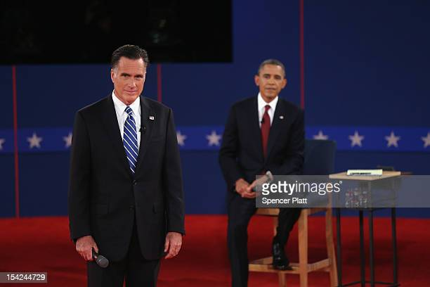 Republican presidential candidate Mitt Romney and U.S. President Barack Obama listen as moderator Candy Crowley of CNN asks a question during a town...