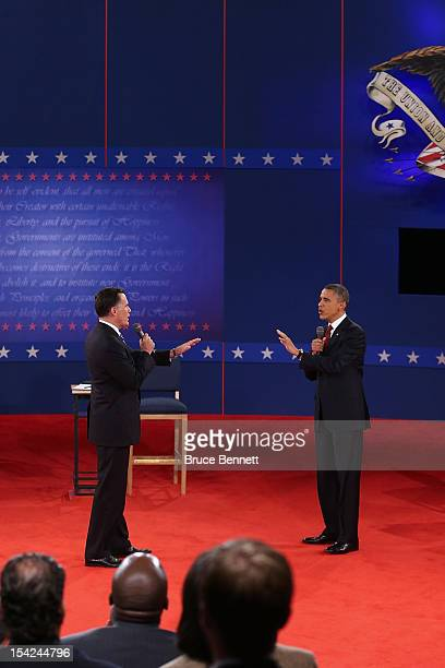 Republican presidential candidate Mitt Romney and US President Barack Obama talk to each other during a town hall style debate at Hofstra University...