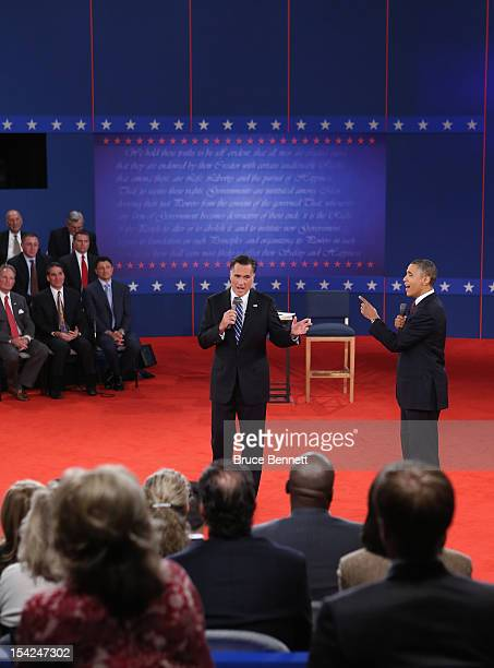 Republican presidential candidate Mitt Romney and US President Barack Obama both talk to the audience during a town hall style debate at Hofstra...