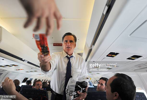 US Republican presidential candidate Mitt Romney hands out beef jerky to journalists on board his campaign plane at the Philadelphia International...