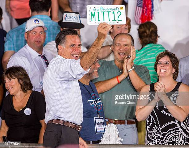 Republican presidential candidate Mitt Romney holds up a supporter's New Hampshire license plate reading MITT12 during a Victory Rally at Holman...