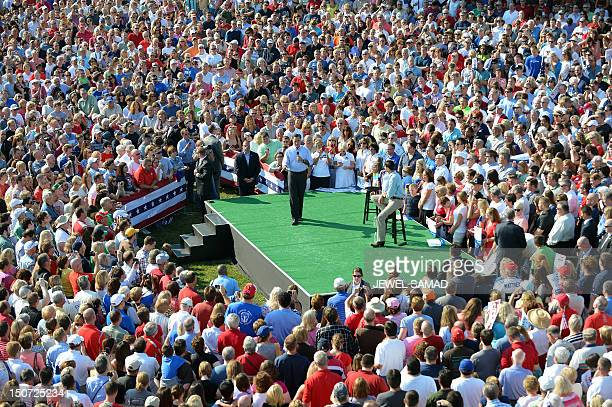 US Republican presidential candidate Mitt Romney speaks as his running mate Paul Ryan and supporters listen during a campaign rally at the village...