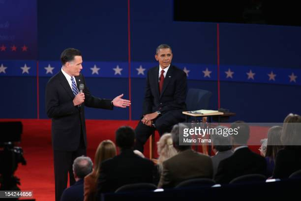 Republican presidential candidate Mitt Romney speaks as US President Barack Obama listens during a town hall style debate at Hofstra University...