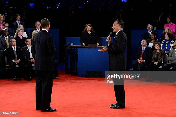 Republican presidential candidate Mitt Romney speaks as US President Barack Obama and moderator Candy Crowley listen during a town hall style debate...