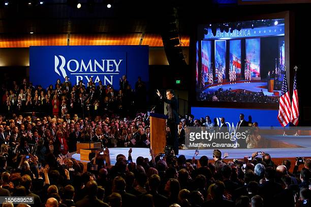 Republican presidential candidate Mitt Romney waves to the crowd while standing at the podium before conceding the presidency during Mitt Romney's...