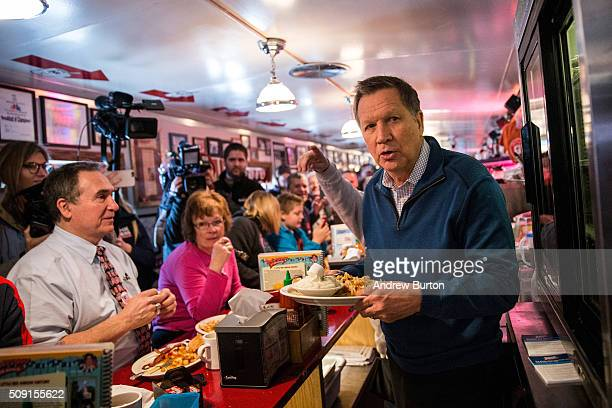 Republican presidential candidate Ohio Governor John Kasich delivers a meal to patrons at the Red arrow Diner on February 9 2016 in Manchester New...