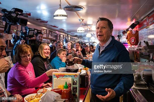 Republican presidential candidate Ohio Governor John Kasich serves coffee to patrons at the Red arrow Diner on February 9 2016 in Manchester New...