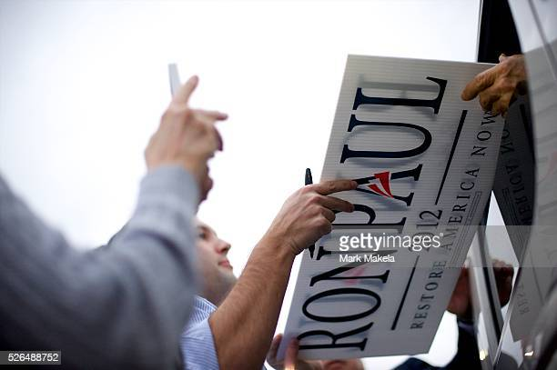 Republican Presidential candidate Ron Paul greets fans from his departing vehicle after holding a town hall meeting at the Holiday Inn in Rock Hill...