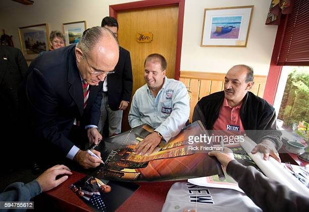 Republican presidential candidate Rudy Giuliani signs autographs while campaigning at the Golden Egg Restaurant in Portsmouth New Hampshire