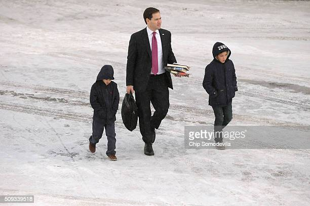 Republican presidential candidate Sen Marco Rubio and his sons Anthony and Dominick walk across the tarmac before departing from ManchesterBoston...