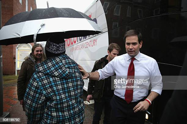 Republican presidential candidate Sen Marco Rubio gives his umbrella to Virginia Sanborn and her mother also named Virginia Sanborn because they were...