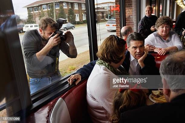 Republican presidential candidate Texas Gov Rick Perry eats lunch with people during a campaign visit to the DriveIn restaurant on January 172012 in...