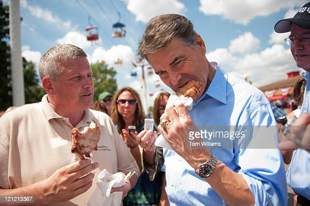 Republican presidential candidate Texas Gov Rick Perry right eats a pork chop with Iowa Secretary of Agriculture Bill Northey for Secretary of...
