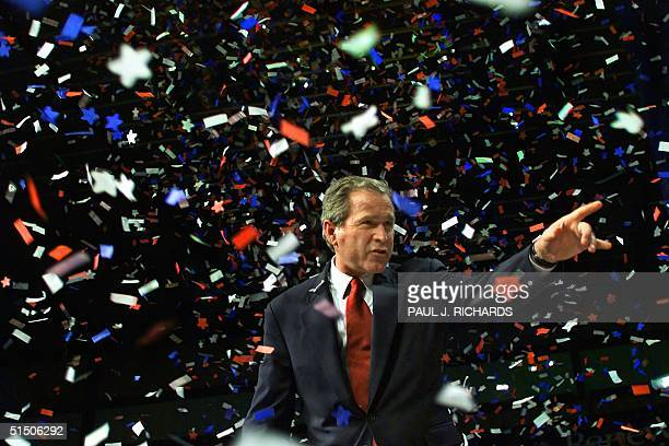 Republican presidential candidate Texas Governor George W Bush points to someone in the crowd as confettii falls while he attends a homecoming party...