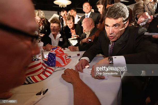 Republican presidential candidate Texas Governor Rick Perry visits with Erl Schmiesing of Waterloo Iowa during the Blackhawk County Republican annual...