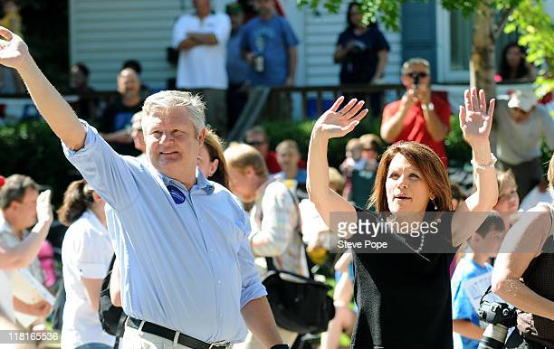 Republican presidential candidate US Rep Michele Bachmann and her husband Marcus Bachmann wave as they march in a Fourth of July parade July 4 2011...