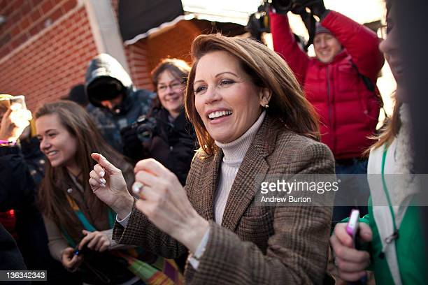 Republican presidential candidate US Rep Michele Bachmann dances with supporters from Taylor High School in Cincinatti Ohio on January 2 2012 in West...