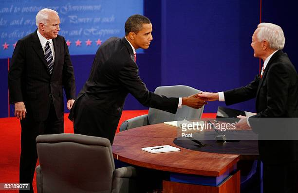 Republican presidential candidate US Sen John McCain loosks on as Democratic presidential candidate US Sen Barack Obama shakes hands with moderator...