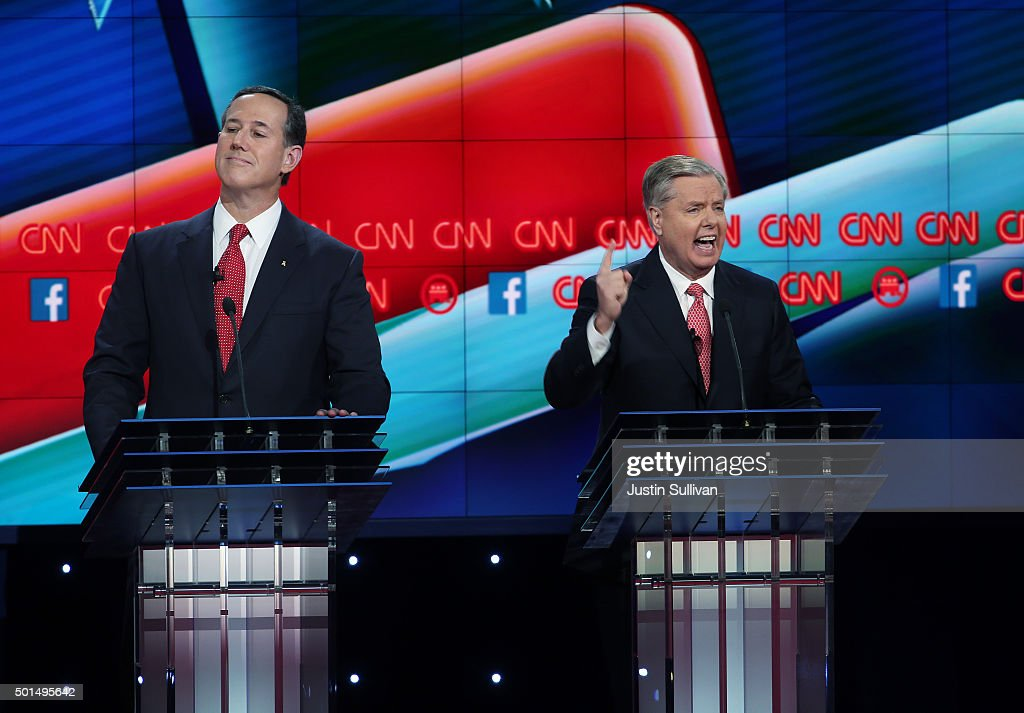 Republican presidential candidate U.S. Sen. Lindsey Graham (R-SC) speaks as Rick Santorum listens during the CNN Republican presidential debate on December 15, 2015 in Las Vegas, Nevada. This is the last GOP debate of the year, with U.S. Sen. Ted Cruz (R-TX) gaining in the polls in Iowa and other early voting states and Donald Trump rising in national polls.