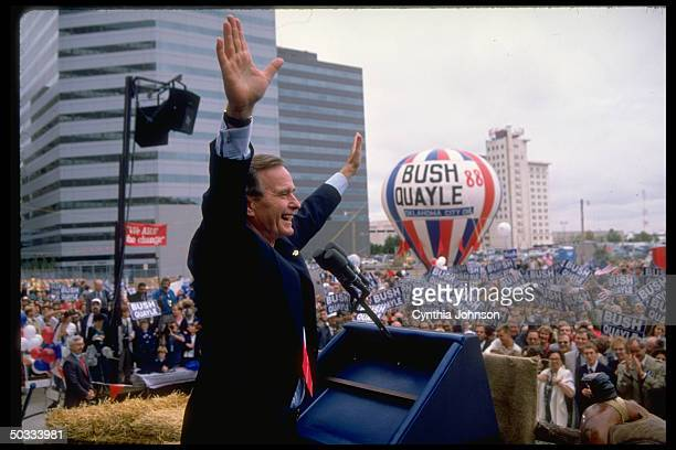 Republican presidential candidate VP George Bush raising arms triumphantly above supportive crowd at campaign rally graced by BUSH QUAYLE 88 hot air...