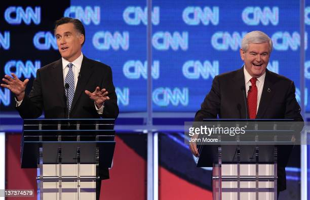 Republican presidential candidates former Massachusetts Gov Mitt Romney makes a point as former Speaker of the House Newt Gingrich laughs during a...