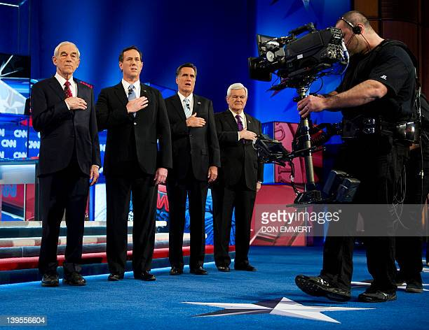 Republican presidential candidates Ron Paul Rick Santorum Mitt Romney and Newt Gingrich listen to the national anthem on February 22 2012 in Mesa...