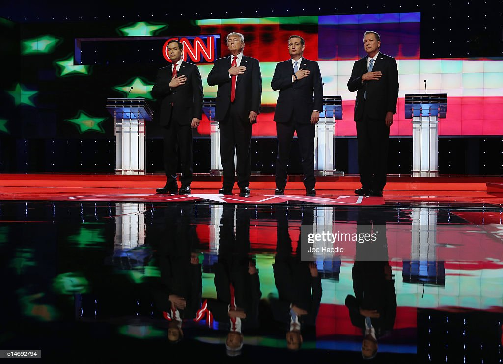 Republican presidential candidates, Sen. Marco Rubio (R-FL), Donald Trump, Sen. Ted Cruz (R-TX), and Ohio Gov. John Kasich listen to the national anthem before the start of the CNN, Salem Media Group, The Washington Times Republican Presidential Primary Debate on the campus of the University of Miami on March 10, 2016 in Coral Gables, Florida. The candidates continue to campaign before the March 15th Florida primary.