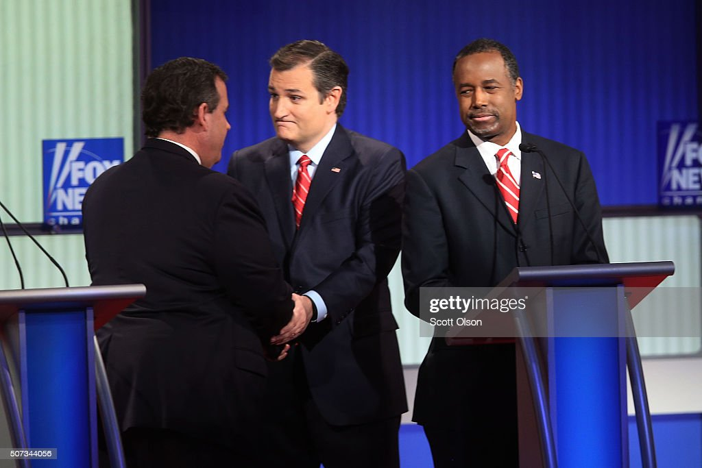 Republican presidential candidates Sen. Ted Cruz (R-TX) (2nd L) shakes hands with New Jersey Governor Chris Christie (L) as Ben Carson (R) looks on after the Fox News - Google GOP Debate January 28, 2016 at the Iowa Events Center in Des Moines, Iowa. Residents of Iowa will vote for the Republican nominee at the caucuses on February 1. Donald Trump, who is leading most polls in the state, decided not to participate in the debate.