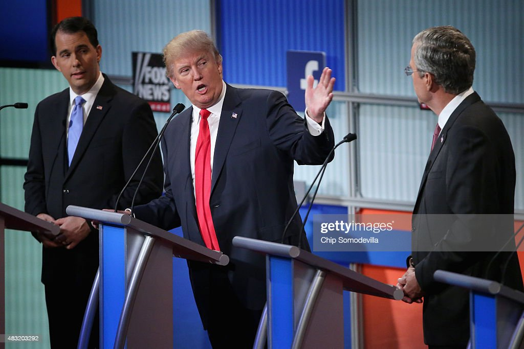 Republican presidential candidates (L-R) Wisconsin Gov. Scott Walker, Donald Trump and Jeb Bush participate in the first prime-time presidential debate hosted by FOX News and Facebook at the Quicken Loans Arena August 6, 2015 in Cleveland, Ohio. The top-ten GOP candidates were selected to participate in the debate based on their rank in an average of the five most recent national political polls.