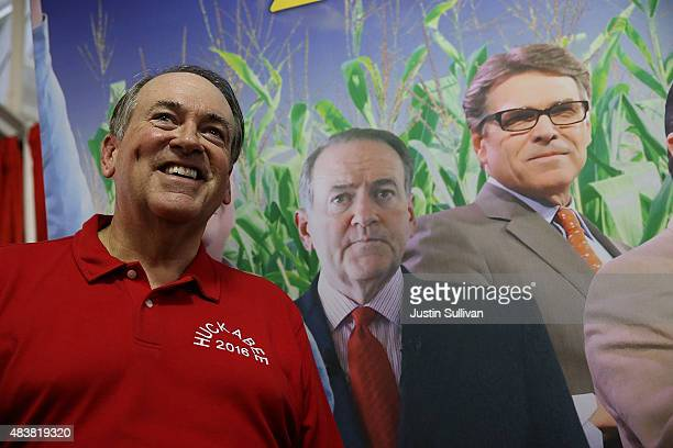 Republican presidential hopeful and former Arkansas Gov Mike Huckabee stands next to a poster featuring all of the republican candidates for...