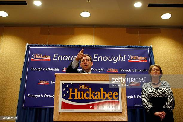 Republican presidential hopeful and former Arkansas Gov. Mike Huckabee speaks during a news conference as his wife Janet looks on at the Marriott...