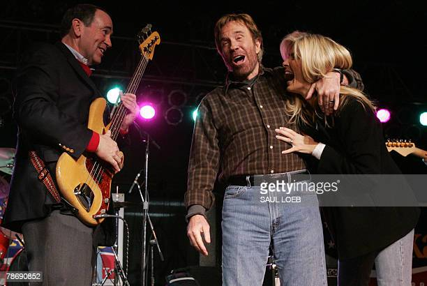 Republican Presidential hopeful and former Arkansas Governor Mike Huckabee jokes with US Actor Chuck Norris and his wife Gena O'Kelley as he plays...