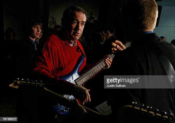 Republican presidential hopeful and former Arkansas Governor Mike Huckabee plays bass guitar with Funk Pod after speaking to a crowd at the...