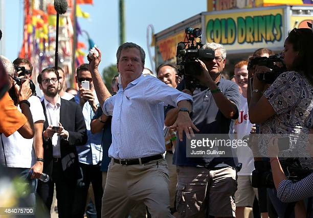 Republican presidential hopeful and former Florida Gov Jeb Bush throws a baseball at as he plays a carnival game during the Iowa State Fair on August...