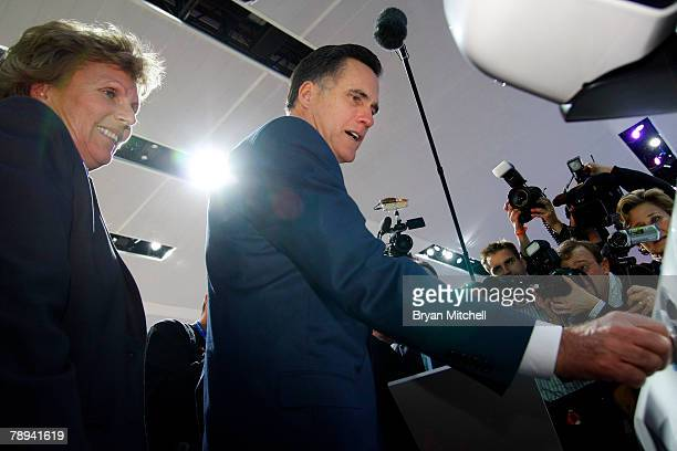 Republican presidential hopeful and former Massachusetts Gov. Mitt Romney puts the cap back on the plug of the Ford Escape plug-in hybrid as Ford's...