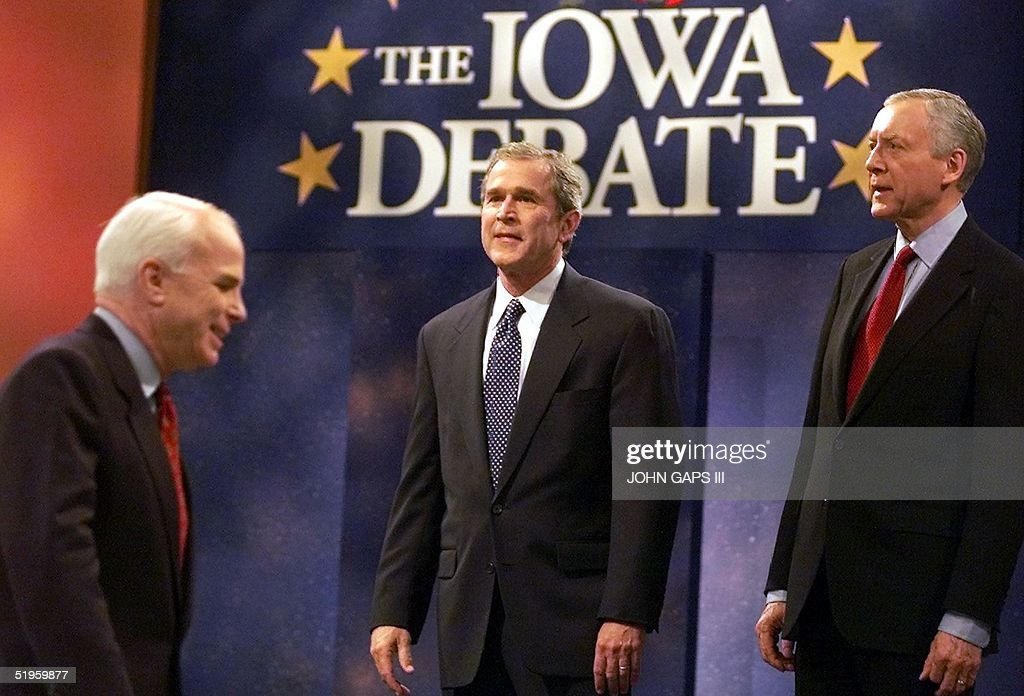 Republican presidential hopeful Arizona Senator John McCain (L) walks by fellow candidates Texas Gov. George W. Bush (C) and Utah Senator Orrin Hatch (R) 13 December 1999 before a debate forum at the Civic Center of Greater Des Moines in Des Moines, Iowa. The Republican presidential hopefuls are debating the issues of the Republican platform for the presidential election in 2000.
