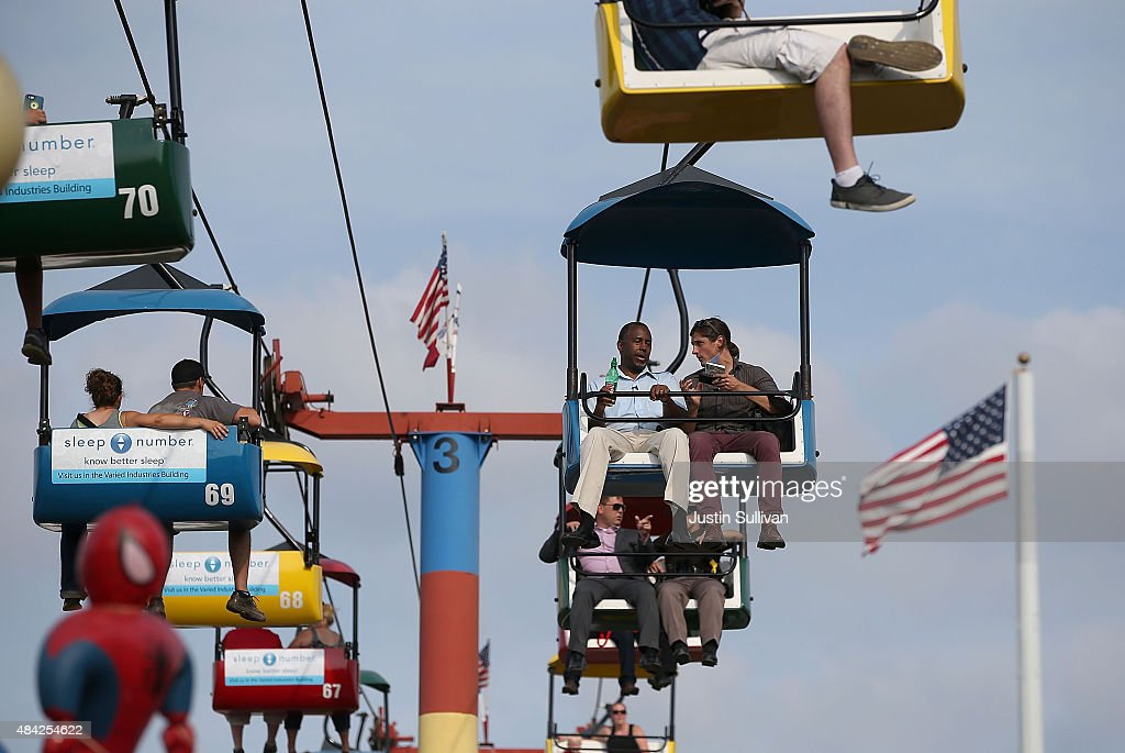Republican presidential hopeful Ben Carson rides the Sky Glider with a reporter while touring the Iowa State Fair on August 16, 2015 in Des Moines, Iowa. Presidential candidates are addressing attendees at the Iowa State Fair on the Des Moines Register Presidential Soapbox stage and touring the fairgrounds. The State Fair runs through August 23.