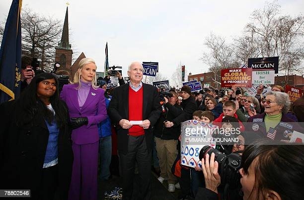 US Republican presidential hopeful John McCain his wife Cindy and their adopted daughter Bridget arrive at a rally in front of the State House in...