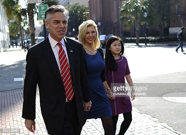 Republican presidential hopeful Jon Huntsman walks with his wife Mary Kaye and daughter Gracie on his way to greet people at Virginia's restaurant in...