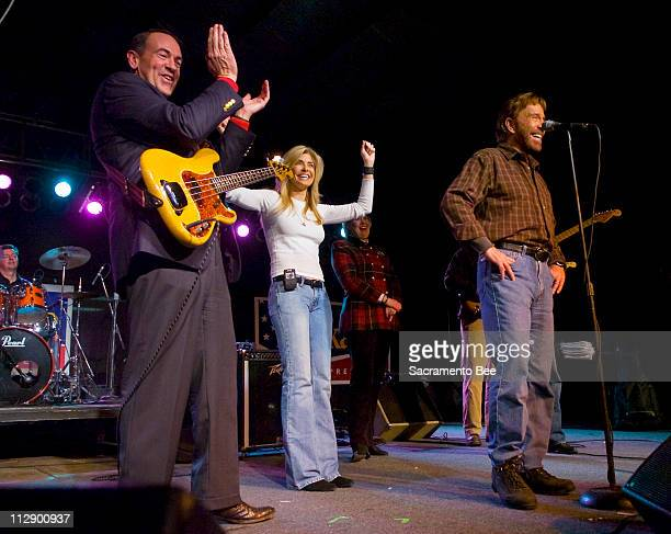 Republican presidential hopeful Mike Huckabee claps while on stage with Chuck Norris and his wife Gena during a rally in West Des Moines Iowa on...