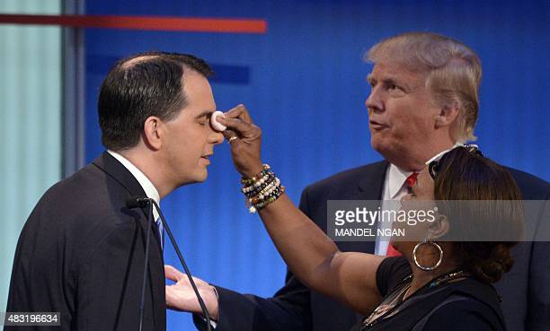 Republican presidential hopeful Scott Walker has makeup applied while speaking to opponent Donald Trump during the prime time Republican presidential...
