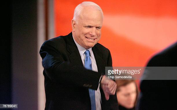Republican presidential hopeful Sen John McCain gives a grimice and a thumbsdown during a break from a televised debate at Saint Anselm College...