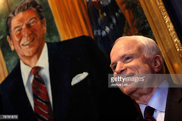 Republican presidential hopeful US Sen John McCain stands next to a painting of former President Ronald Reagan at the Reagan Day Dinner at the...