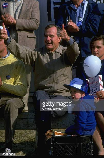 Republican presidential hopeful VP George Bush proferring double thumbsup sitting in stands w daughter Dorothy LeBlond grandson Sam in campaign...