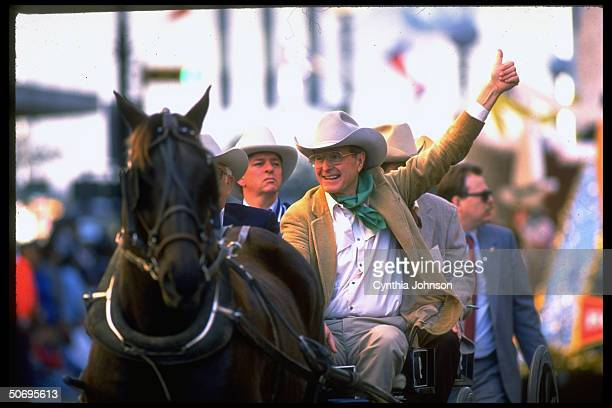 Republican presidential hopeful VP George Bush sporting cowboy garb proferring thumbsup riding in horsedrawn vehicle in campaign rodeo parade...