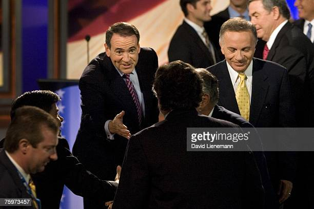 Republican Presidential hopefuls former Arkansas Governor Mike Huckabee and US Rep Tom Tancredo talk to a reporter after a special debate edition of...