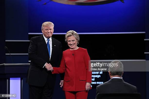 Republican presidential nominee Donald Trump and Democratic presidential nominee Hillary Clinton shake hands prior to the start of the Presidential...