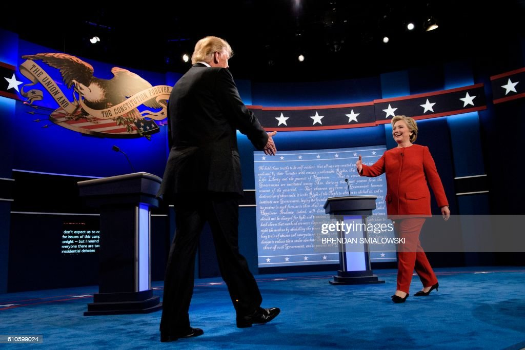 TOPSHOT - Republican presidential nominee Donald Trump (L) and Democratic presidential nominee Hillary Clinton greet each other before the first US Presidential Debate at Hofstra University September 26, 2016 in Hempstead, New York. / AFP PHOTO / Brendan Smialowski